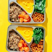 Vegetarian meal prep with roasted chickpeas, quinoa, yellow sauce, and spinach on a yellow background