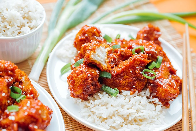 General Tso's cauliflower on a plate with rice and green onions