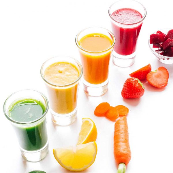 Rainbow smoothie shots with fruits and veggies on a white background