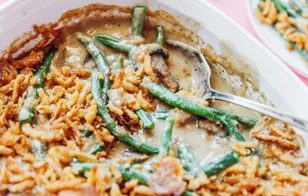 A metal spoon dipped into a casserole dish filled with vegan green bean casserole