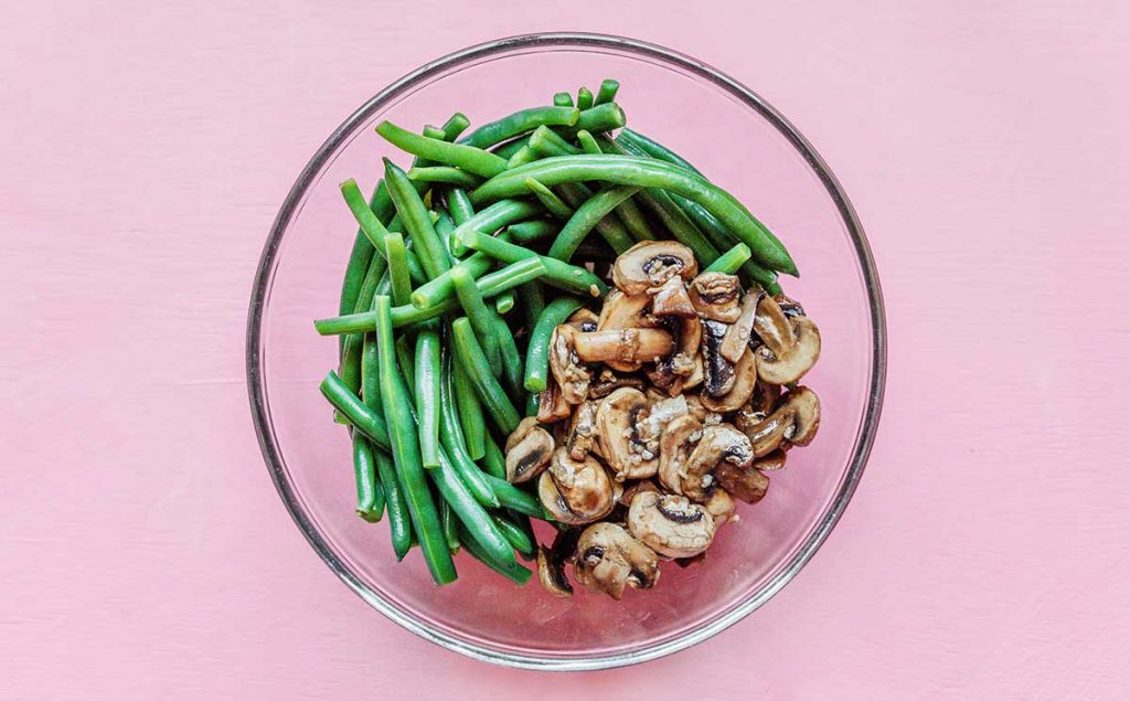 A clear glass bowl filled with green beans and sautéed mushrooms