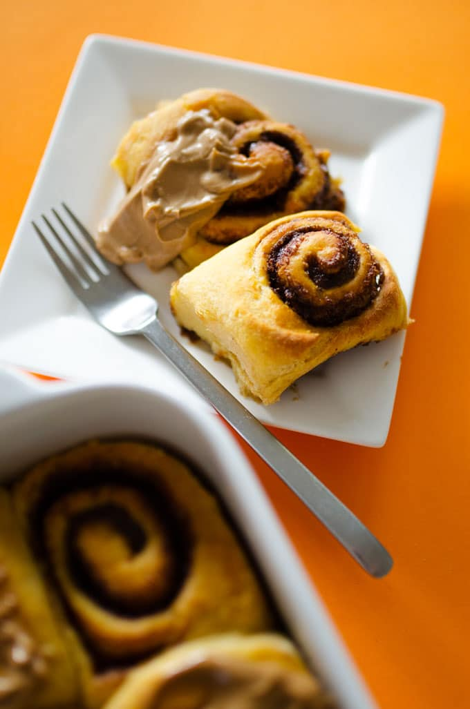 Cinnamon rolls on a plate with a fork - Fluffy, decadent, in slathered in a simple brown sugar cream cheese frosting, these Sweet Potato Cinnamon Rolls are the perfect way to wake up.