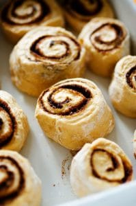 Raw cinnamon rolls in a white pan - Fluffy, decadent, in slathered in a simple brown sugar cream cheese frosting, these Sweet Potato Cinnamon Rolls are the perfect way to wake up.