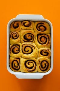 Cinnamon rolls in a pan on an orange background - Fluffy, decadent, in slathered in a simple brown sugar cream cheese frosting, these Sweet Potato Cinnamon Rolls are the perfect way to wake up.