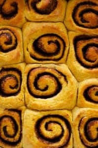 Closeup of cinnamon rolls in a pan - Fluffy, decadent, in slathered in a simple brown sugar cream cheese frosting, these Sweet Potato Cinnamon Rolls are the perfect way to wake up.