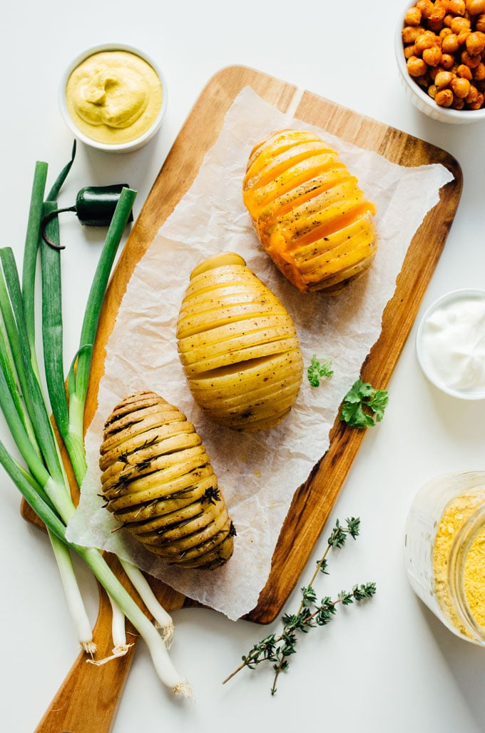 Hasselback potatoes on a cutting board - Change up the routine and make these easy hasselback potatoes for dinner tonight! We're whipping up three tasty flavors: vegan nacho, herb, and loaded.