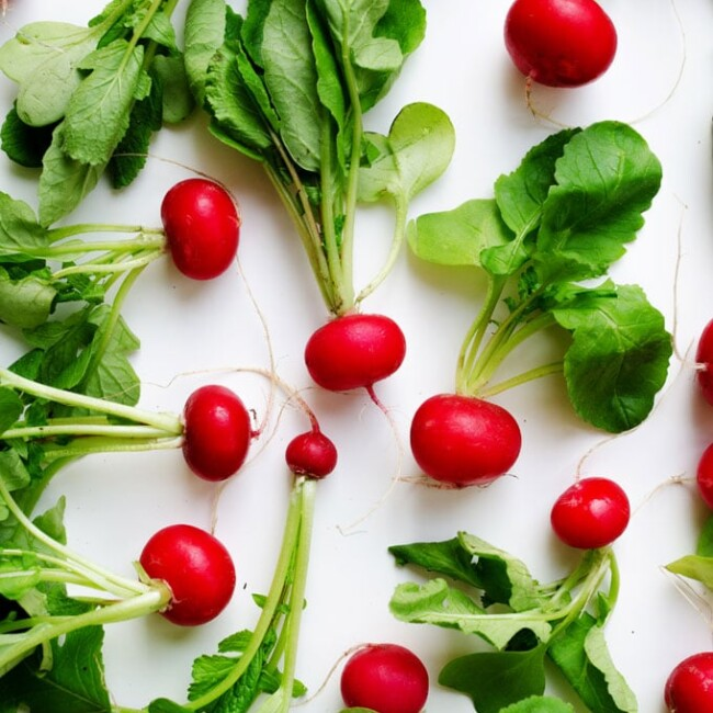 red radishes on a white background - These radish recipes are simple and delicious (and best of all, they'll make you actually WANT to eat your veggies!) Give them a try for a colorfully peppery crunch.