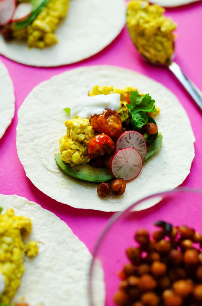 "Vegan tofu scramble tacos on a pink background - These Vegan Breakfast Tacos are stuffed with flavorful tofu scramble, ""bacon-y"" crispy chickpeas, and smoky roasted tomatoes (all in under 30 minutes!)"
