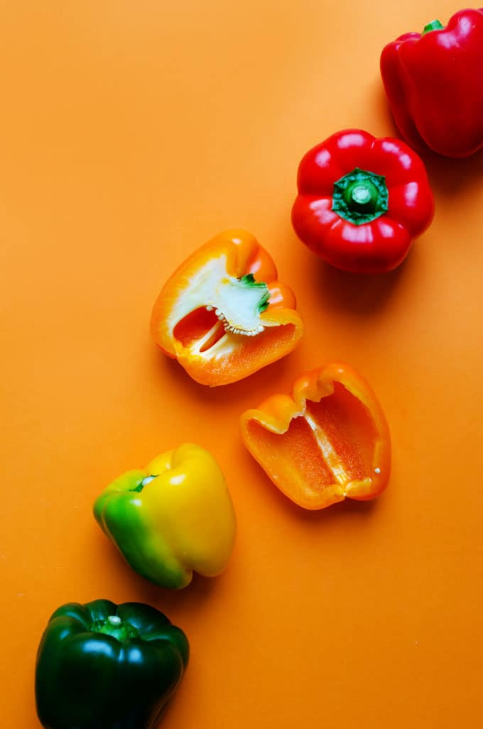 Colorful bell peppers on an orange background - Need a healthy vegetarian dinner outside of your usual routine? These Enchilada Quinoa Stuffed Peppers flavored with a quick homemade enchilada sauce and baked to bubbly, cheesy, perfection.