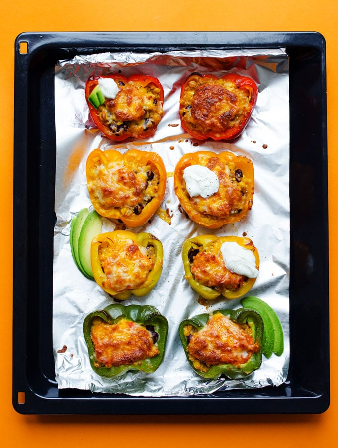 Quinoa stuffed peppers on a baking sheet with melted cheese, sour cream, and avocado.