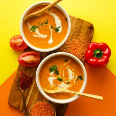 This Roasted Red Pepper Soup draws inspiration from the delicious Spanish pepper sauce, romesco! With smoky roasted peppers, juicy Roma tomatoes, and a dollop of almond butter, this is a creamy soup that gets a delicious dinner on the table (in under 15 minutes!)