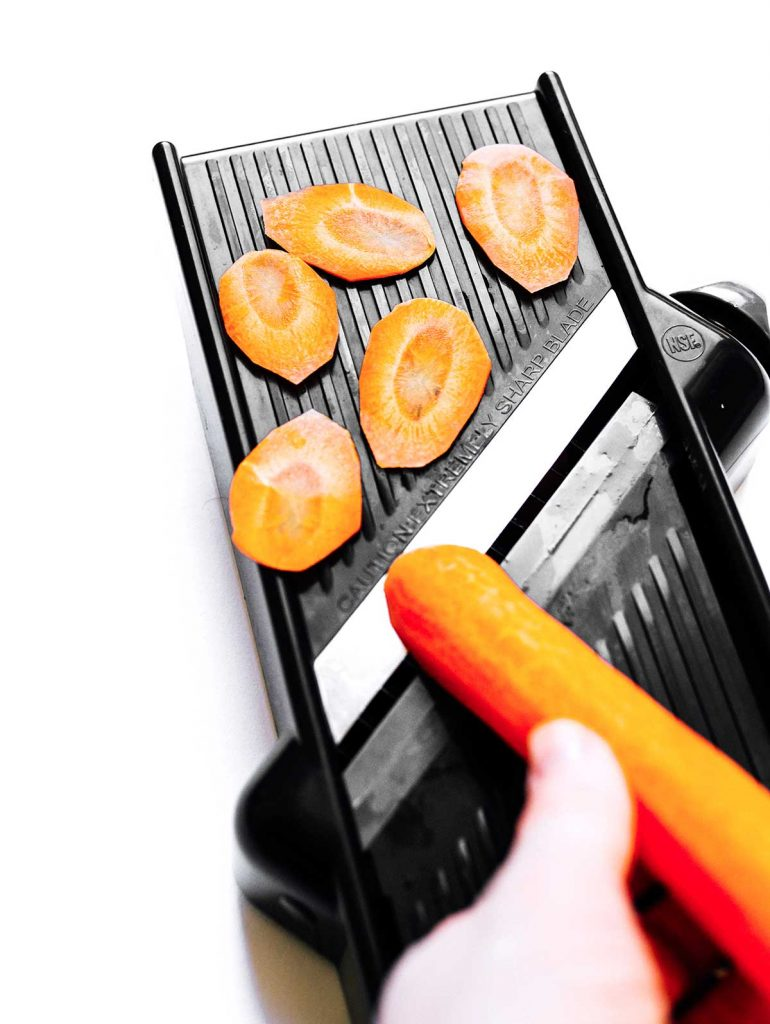 Slicing carrots into chips with a mandoline slicer