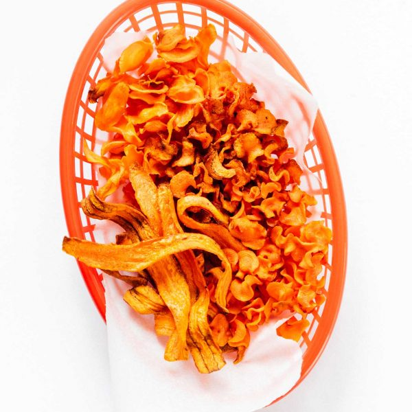 Carrot chips in a basket on a white background