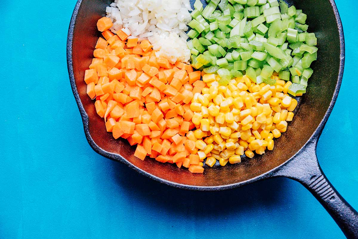 Carrots, corn, celery, and onion in a cast iron skillet with a blue background