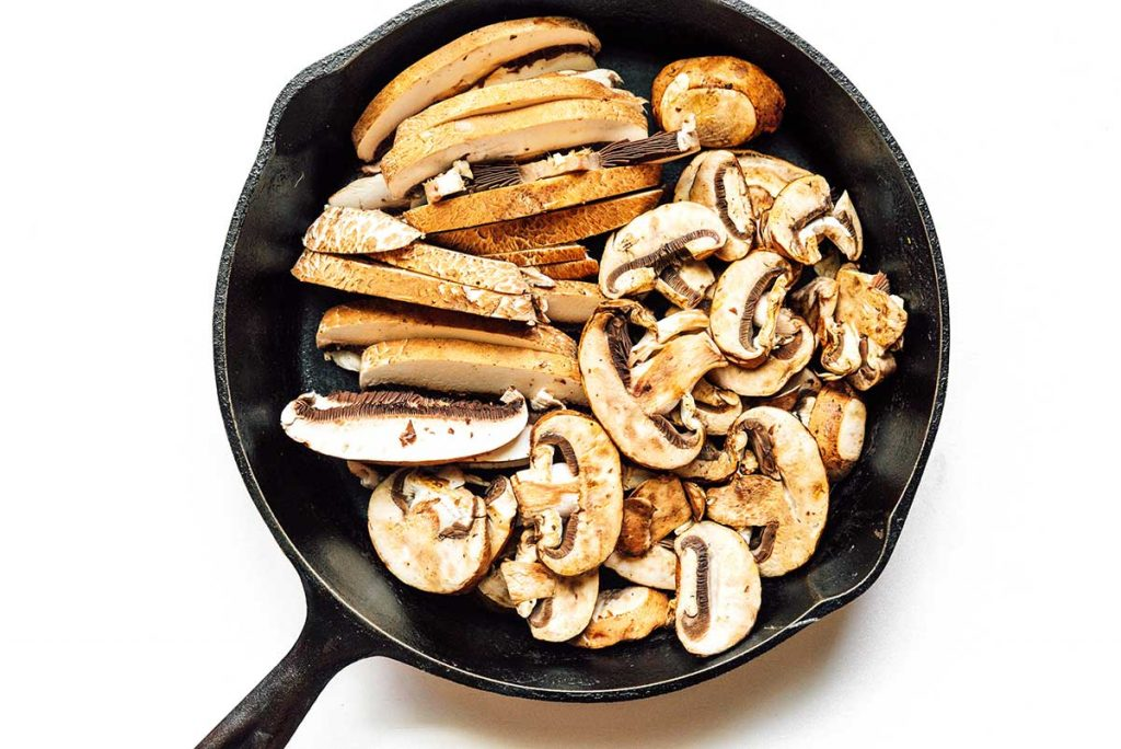 A cast iron skillet filled with sliced mushrooms.