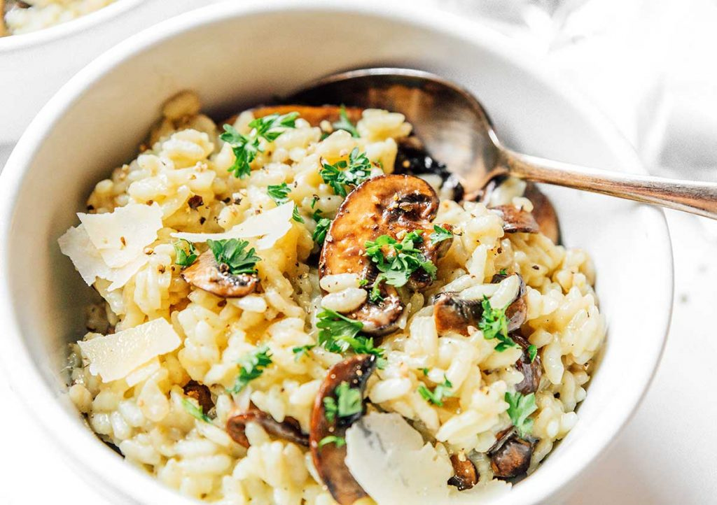 A white bowl filled with mushroom risotto and topped with parmesan flakes.