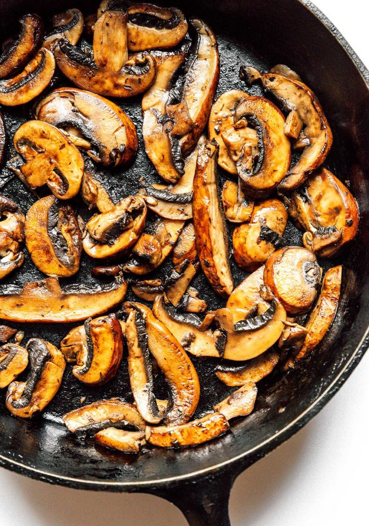 A cast iron skilled filled with cooked sliced mushrooms.