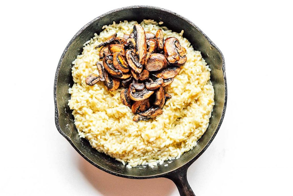 A cast iron skillet filled with cooked, fluffy risotto and topped with cooked mushroom slices.