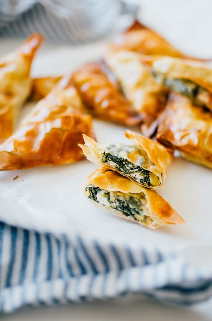 How to make spanakopita, cut one on a white plate with a blue towel - These Spanakopita Triangles are a simple appetizer jam-packed with feta and spinach, wrapped up in buttery, flaky phyllo crust.