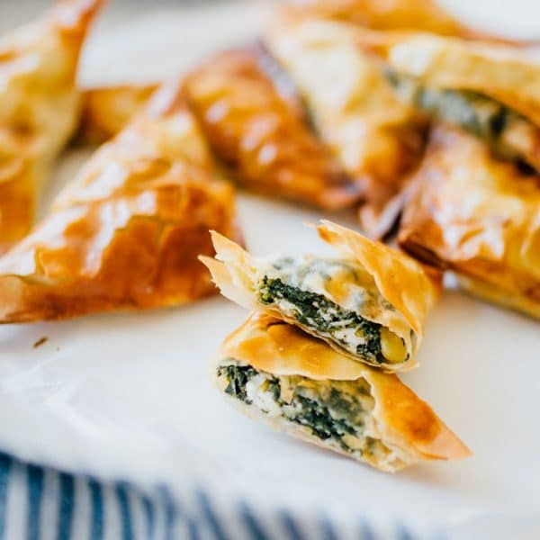 How to make spanakopita, cut opne on a white plate with a blue towel - These Spanakopita Triangles are a simple appetizer jam-packed with feta and spinach, wrapped up in buttery, flaky phyllo crust.