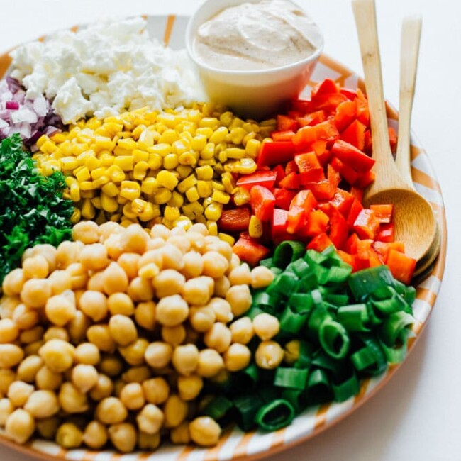 Salad ingredients on a plate on a white background - Today we're whipping up a Chickpea Corn Salad that's bursting with veggies and herbs, and tied together with a spiced Greek yogurt dressing.