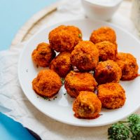 Buffalo mushroom poppers on a white plate with a blue background - These Buffalo Mushroom Poppers are stuffed with creamy jalapeno filling, coated in a quick panko crust, baked to crispy perfection, and topped off with buffalo sauce and bleu cheese dipping sauce.