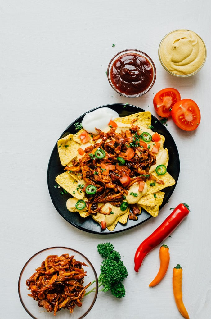 "Vegan nachos on a black plate on a white background - These vegan nachos are piled high with easy mushroom BBQ ""pulled pork"" and a cashew-based queso cheese sauce that will knock your dairy-free socks off."
