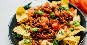 """Vegan nachos on a black plate on a white background - These vegan nachos are piled high with easy mushroom BBQ """"pulled pork"""" and a cashew-based queso cheese sauce that will knock your dairy-free socks off."""