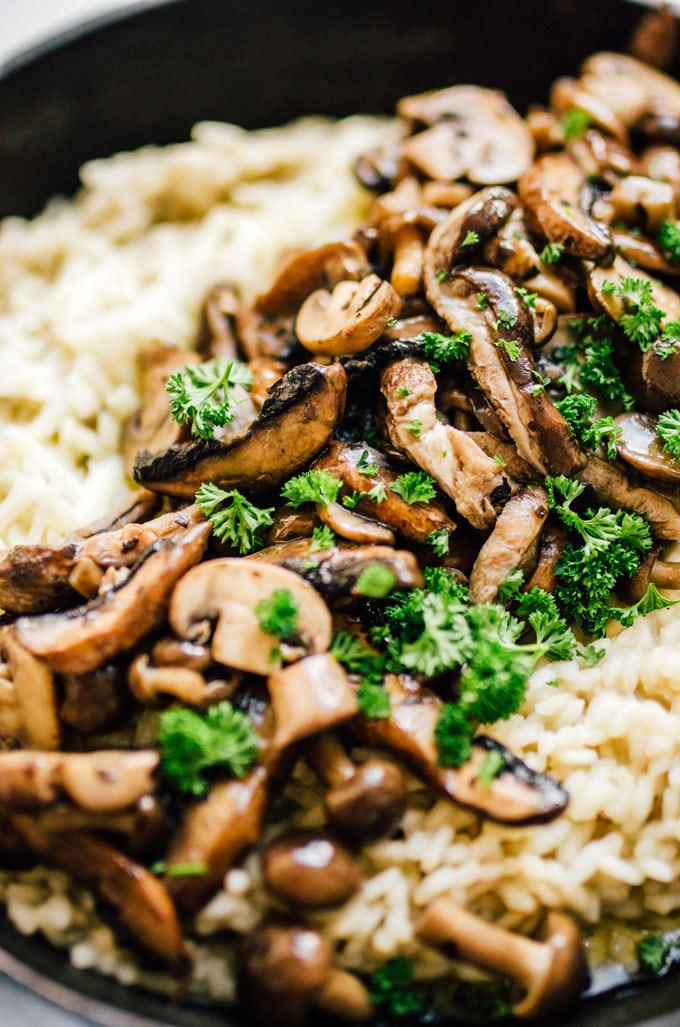 Closeup photo of adding mushrooms to risotto in a cast iron skillet