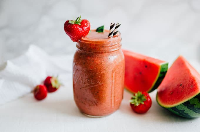 Watermelon rind smoothie with strawberries on a white background and a paper straw