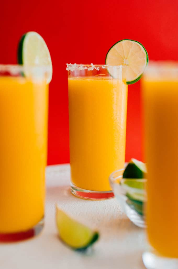 Frozen mango margarita slush in a glass with a slice of lime on a red background