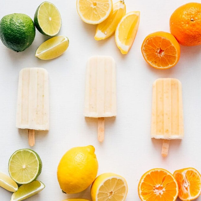 Lime, lemon, and orange creamsicle popsicles on a white background with citrus fruit