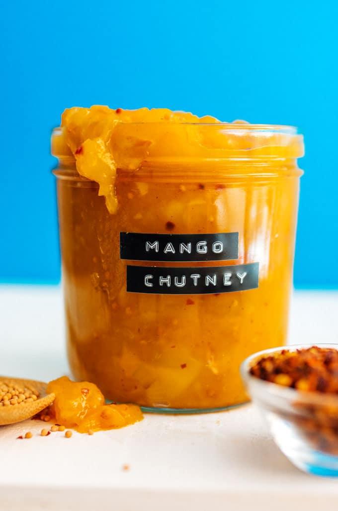 Labeled jar of mango chutney on a blue background