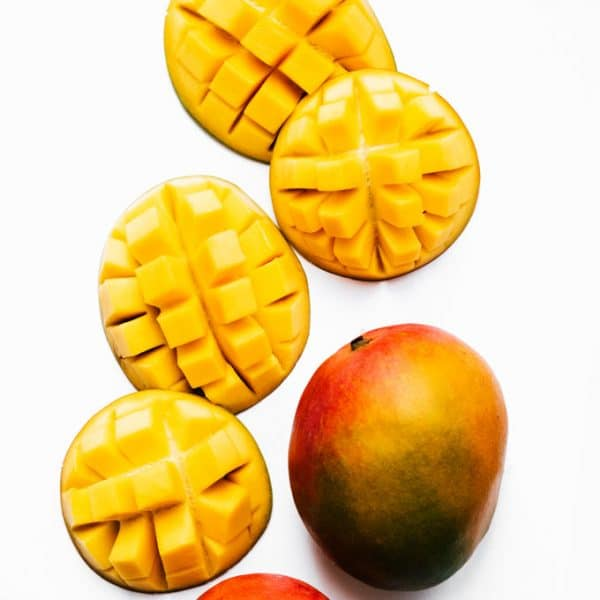 Cut mangoes on a white background