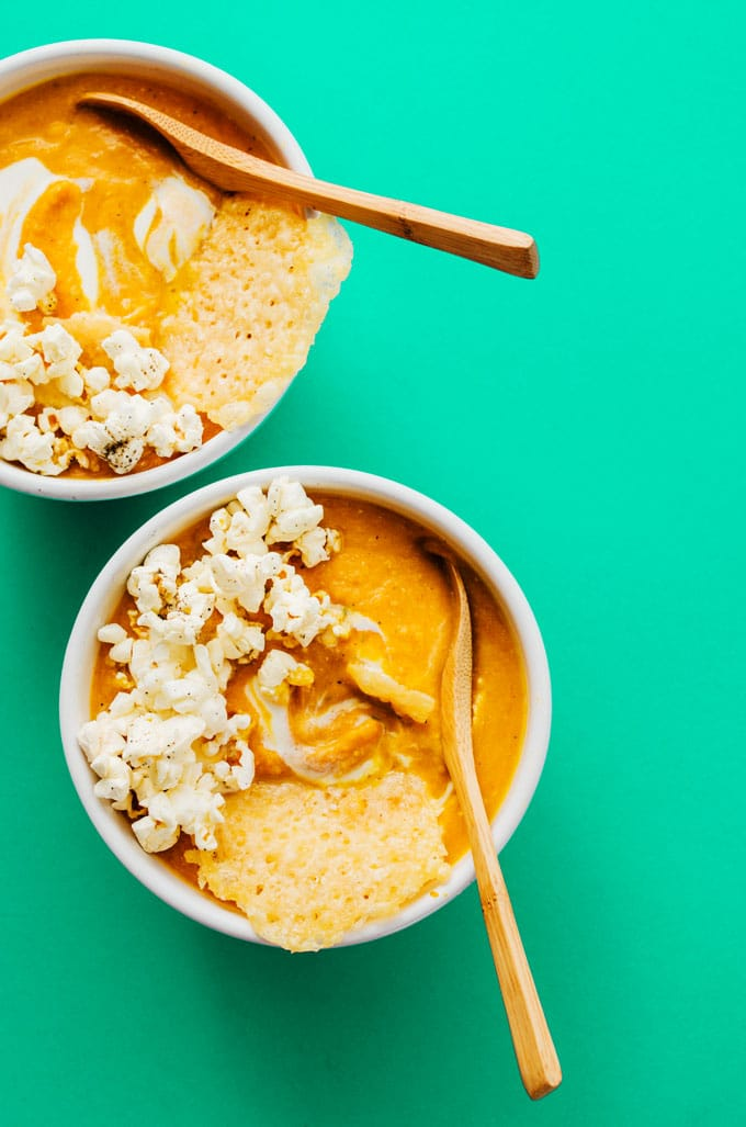 This easy pumpkin soup is topped with parmesan crisps and lightly salted popcorn, transforming simple soup into a fun and memorable dinner for holiday get-togethers.