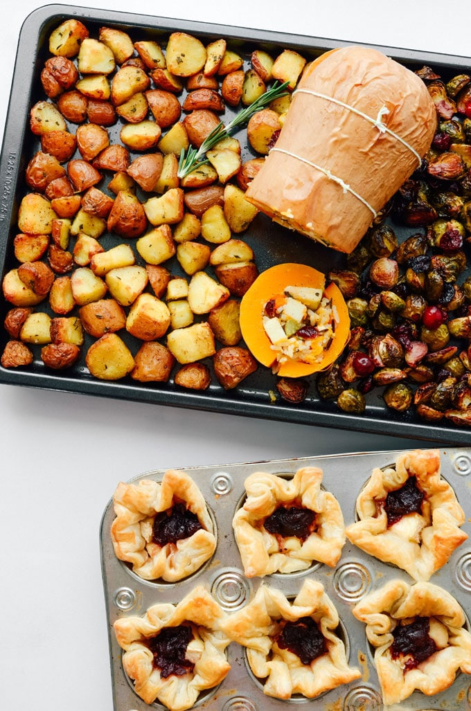 Stuffed butternut squash vegetarian Thanksgiving main dish with crispy potatoes and Brussels sprouts on a baking sheet