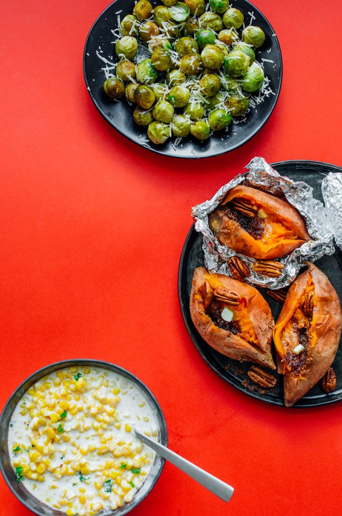Thanksgiving side dishes on a red background, including sweet potatoes, brussels sprouts, and creamed corn