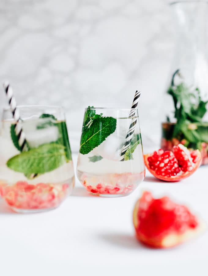 Pomegranate mint water in a glass with a black striped straw