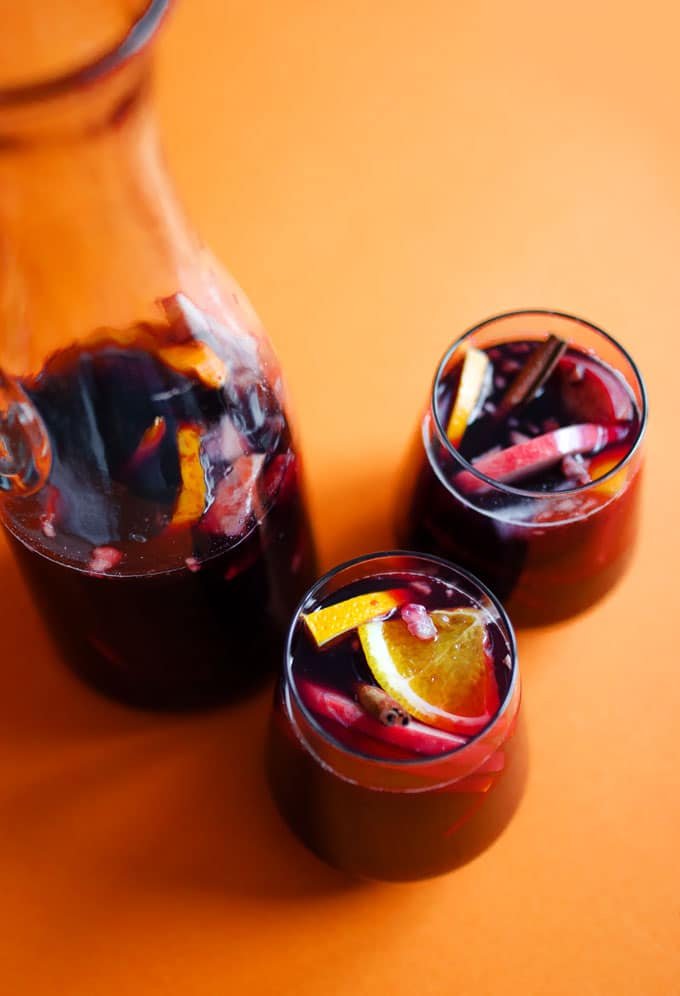 Winter sangria in a wine glass on an orange background