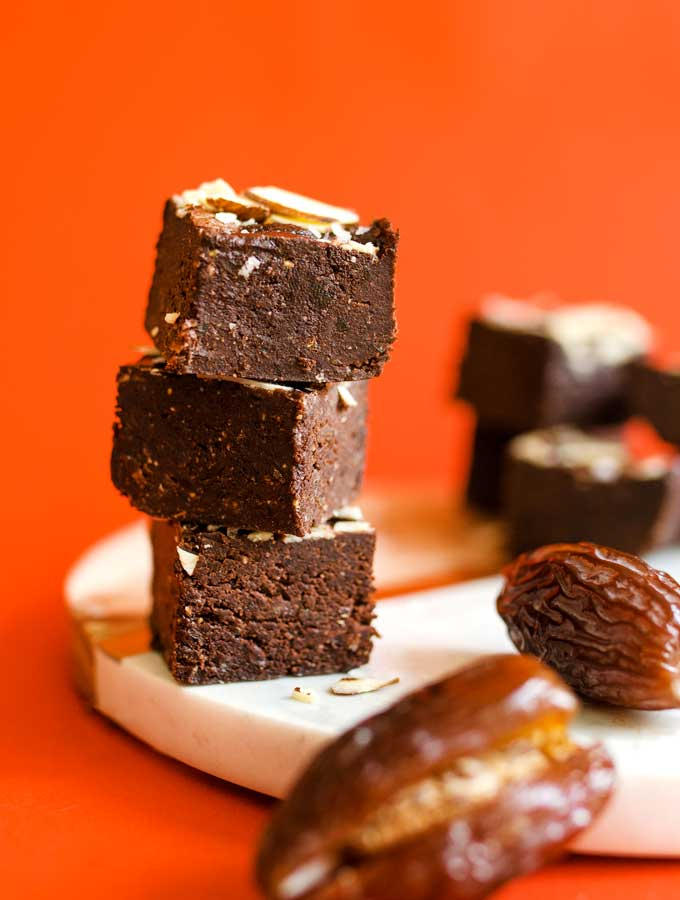 Chocolate fudge with almonds stacked on a red background