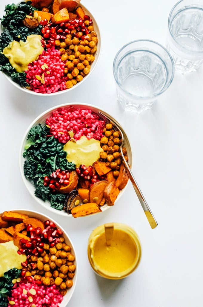 Buddha bowls with pink couscous, roasted chickpeas, sweet potato, kale, and yellow yumm sauce on a white background.