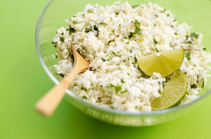 Cauliflower rice with cilantro and lime in a glass bowl on a green background