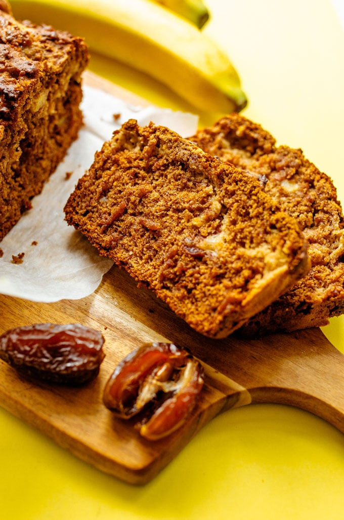 Banana bread slices on a wooden cutting board with yellow background
