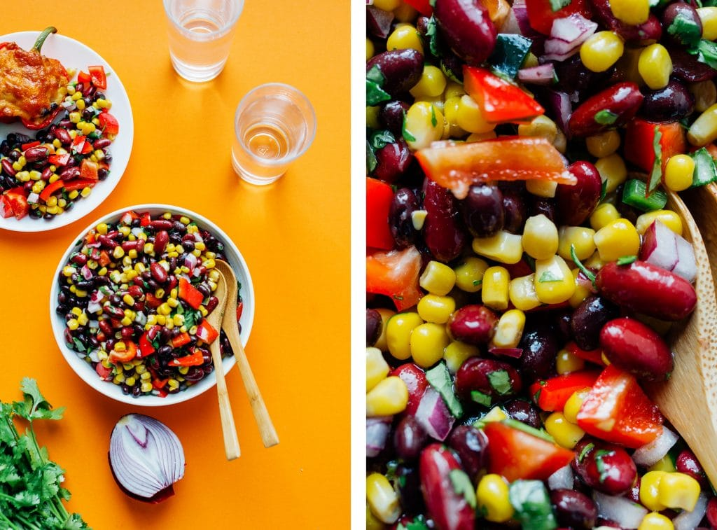 Bean salad in a glass bowl on orange background - This easy Bean Salad recipe is famous in our house, and for good reason! Quick to make, packed with flavor, and perfect for bringing to potlucks!