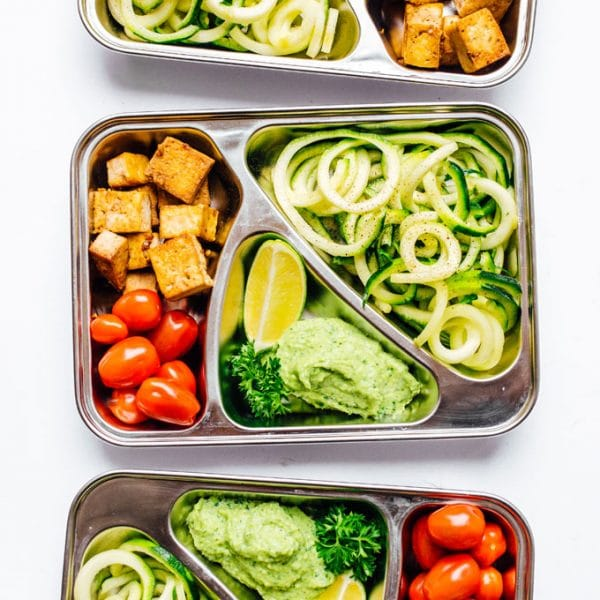 Meal prep container with zucchini noodles on white background - This Zucchini Noodles Vegetarian Meal Prep is a low carb lunch solution that will have you looking forward to lunchtime! Packed with fresh veggies, avocado pesto, and crispy baked tofu.