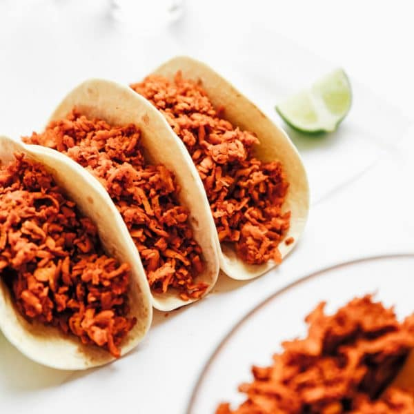 Vegan tempeh taco meat in taco shell on white background