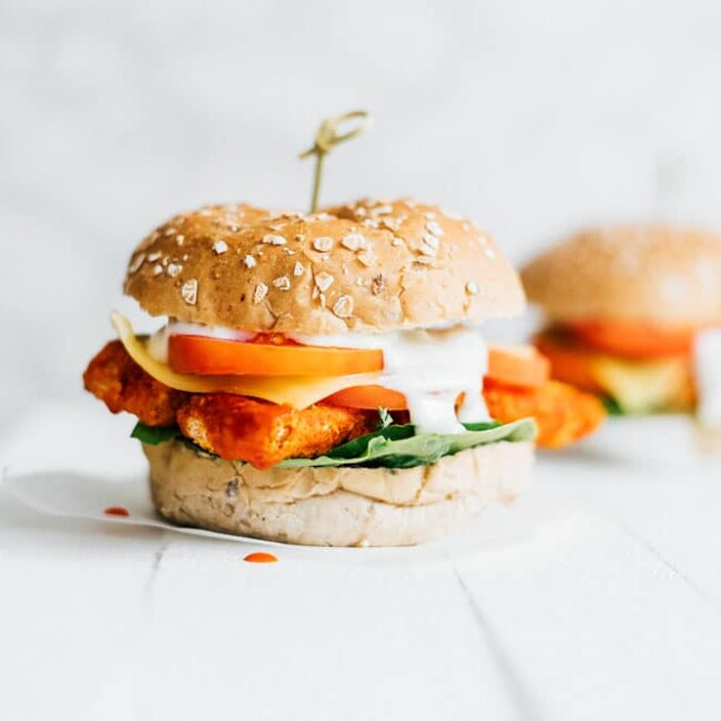 Vegetarian buffalo sandwich on white background - These Buffalo Tempeh Sandwiches are stuffed with crispy baked tempeh buffalo tenders, provolone cheese, and ranch dressing!