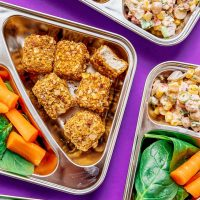 Meal prep boxes on purple background - Vegetarian meal prep that's sure to keep you full all day. Almond crusted tofu nuggets paired with a creamy, veggie-packed chickpea corn salad!