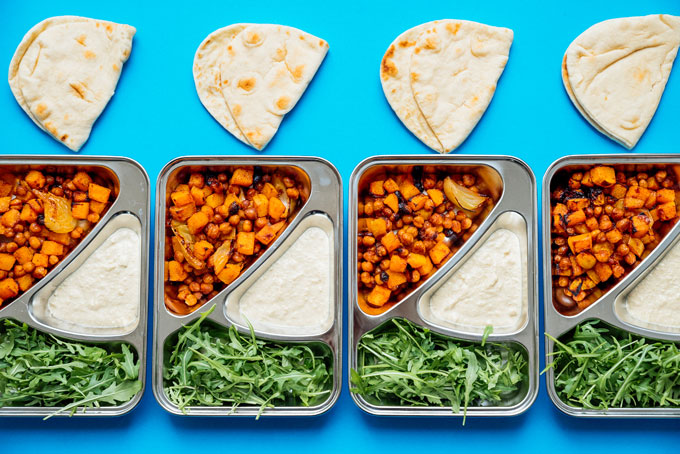 Meal prep containers on a blue background full of butternut squash, hummus, and arugula