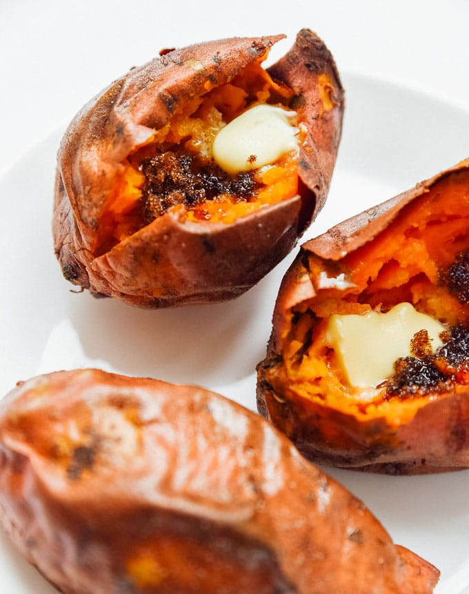 Air fryer sweet potatoes on a white background with butter and brown sugar